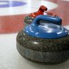 Thumb curling stones on rink with visible pebble